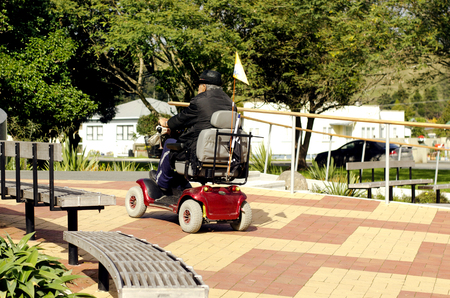 KAITAIA, NZ - AUG 15:Elderly man drive mobility scooter on Aug 15 2013.Currently the US Medicare will not approve a power wheelchair for persons who do not need to use the chair inside their own home.