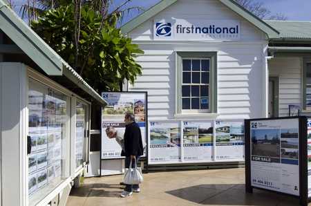 accommodation broker: MANGONUI,NZ - AUG 24:Couple looks at house listing on a signpost of Real Estate office on Aug 24 2013.NZ house prices are booming with the average price of an Auckland city home rocketing to $735,692. Editorial