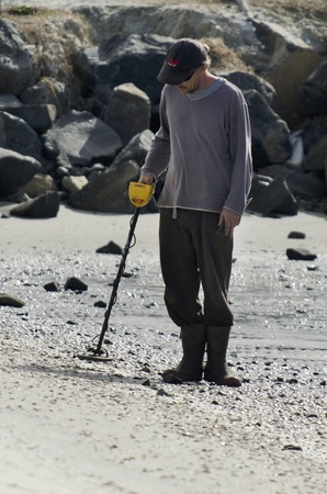 valuable: WHANGAREI,NZ - JULY 28:Man using a metal detector on July 28 2013.Its a popular hobby around the world for  treasure hunting, lost jewelry and other valuable items. Editorial