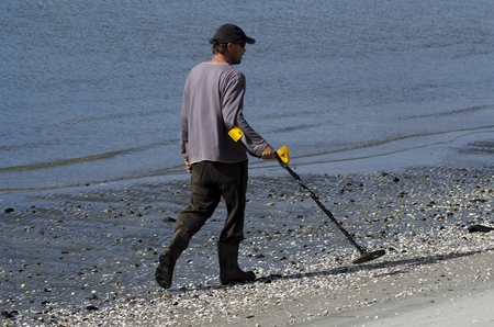 metal detector: WHANGAREI,NZ - JULY 28:Man using a metal detector on July 28 2013.Its a popular hobby around the world for  treasure hunting, lost jewelry and other valuable items. Editorial