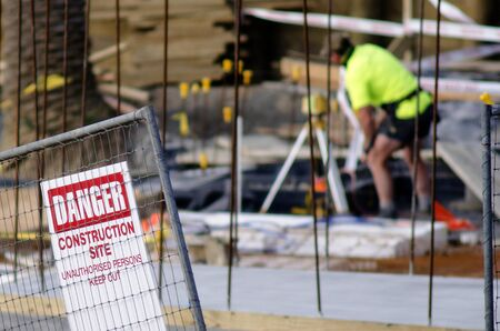 site: AUCKLAND, NZ -JULY 29: Construction site safety sign and worker without hard hat on July 29 2013.Construction is one of the most dangerous land-based work sector in the world. Editorial