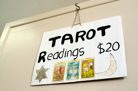 astrologist: MANGONUI , NZ - SEP 07:Tarot card reader sign on a wall on Sep 07 2013.Tarot cards came about in Europe as far back as the late 1300Õs as a result of playing cards being introduced from China.