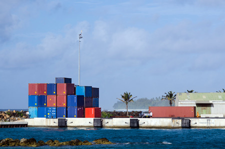 dockside: RAROTONGA - SEP 21:Cargo containers in Port of Avatiu in Rarotonga on Sep 21 2013.Its the international port of Cook Island, which handles 90% imports by sea.