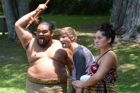 national trust: WAITANGI, NZ - FEB 06:Tourist having fun with Maori people on February 6 2014 in Waitangi NZ.Its a New Zealand public holiday to celebrate the signing of the Treaty of Waitangi in 1840.