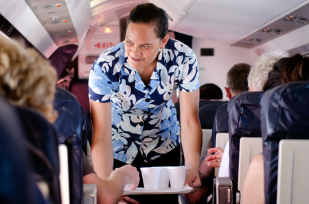 airline hostess: AITUTAKI - SEP 17:Air Rarotonga air hostess serves hot drinks during flight on Sep 17 2013.The airline transport 70,000 passengers between the Cook Islands and other Islands in the Pacific each year