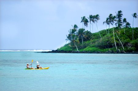 largely: RAROTONGA - SEP 16:Couple kayaking over Muri Lagoon in Rarotonga on Sep 16 2013.Cooks Islands are largely unspoiled by tourism with 100,000 visitors a year.They one of the worlds most remote Islands.