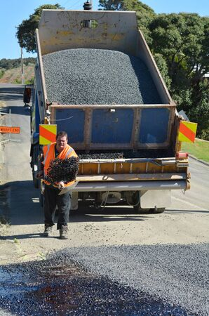 roadwork: CABLE BAY, NZ - APR 01 2014:Road worker spreading new gravel during roadwork. There are more than four million miles of highways and roads in the U.S alone.