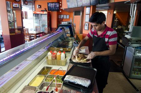 comida gourmet: AUCKLAND, Nueva Zelanda - 07 de octubre: Hombre preparar kabab doner el 07 de octubre de 2013.It y otomana un plato turco desde el siglo 18. El giroscopio griega, shawarma árabe, y mexicana de tacos al pastor se derivan de este plato Editorial