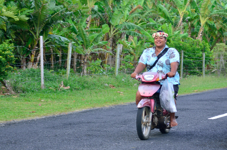 islander: AITUTAKI - SEP 18 2013:Cook Islander woman rids motorbike. Aitutaki is the second most visited island of the Cook Islands.It has a population of approximately 2,000 people. Editorial