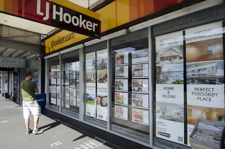 house prices: AUCKLAND,NZ - OCT 06:Man looks at house listing on a signpost of Real Estate office on Oct 06 2013.NZ house prices are booming with the average price of an Auckland city home rocketing to $735,692. Editorial