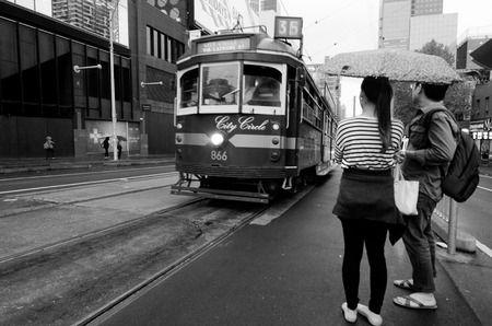 tramcar: MELBOURNE,AUS - APR 10 2014:Passengers and the W class tram in City Circle service.Its a zero-fare tram  aimed mainly for tourists running around the central business district of Melbourne,Australia. Editorial