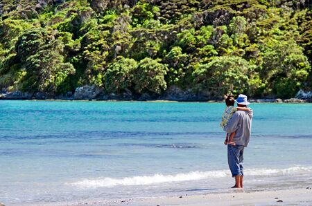 destress: Man hold his child on Rangiputa beach in Karikari Peninsula Northland,New Zealand.Its a famous holiday travel destination in NZ.