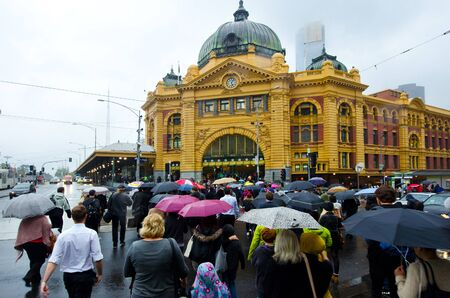 flinders: MELBOURNE, AUS - APR 10 2014:Pedestrians cross Flinders Street towards Flinders Street railway station.Its on of the most busiest pedestrian crossings in Australia and the busiest of Melbournes. Editorial