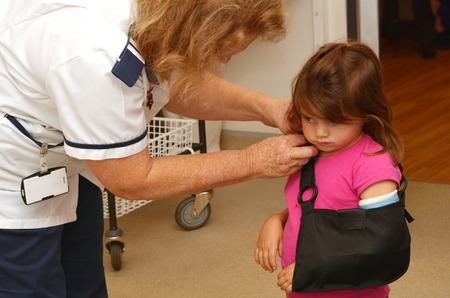 cast: KAITAIA, NZ - MAR 17:Nurse apply a sling over orthopedic cast of a little girl Talya Ben-Ari age 3 in hospital room on Mar 06 2014.Forearm fractures account for 40 to 50 of all childhood fractures. Editorial