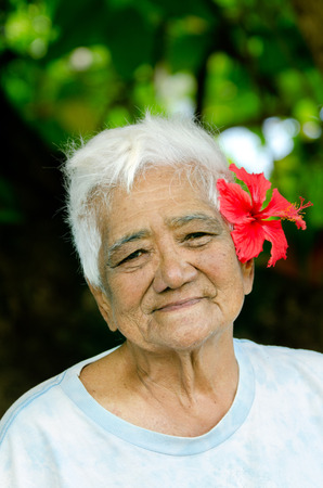 RAROTONGA - SEP 21:Exotic flower,Hibiscus , on old Cook Islander woman hair on Sep 21 2013.The Cook Islands' main population centres are on the island of Rarotonga 14,153 in 2006.