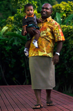 rarotonga: RAROTONGA - SEP 16:Fijian man carry his son on Sep 16 2013.Fijian people are the major indigenous people of the Fiji Islands since 3,500 years ago. Editorial