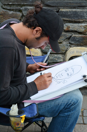 satire: QUEENSTOWN, NZ - JAN 15:Caricature artist on Jan 15 2014.Caricature appeared in th 16th century and today many popular graphic artists have combined caricature with social and political satire. Editorial