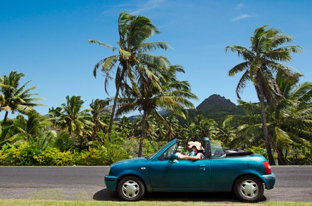 largely: RAROTONGA - SEP 17:Couple travel by car in Rarotonga Island on Sep 17 2013.Cooks Islands are largely unspoiled by tourism with 100,000 visitors a year.They one of the worlds most remote Islands.