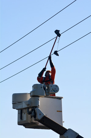 vandalism: KAITIA, NZ - MAR 06:Electric engineer remove an old shoes from power line on Mar 06 2014.Shoe tossing is a common youth vandalism act of throwing a pair of shoes onto telephone wire or power lines.