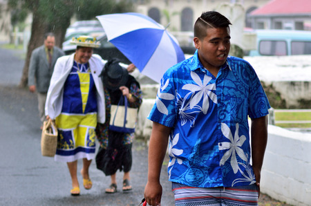 islanders: RAROTONGA - SEP 16 2013:Cook Islanders walks in tropical rain.The Cook Islands main population centers are on the island of Rarotonga (14,153 in 2006) Editorial