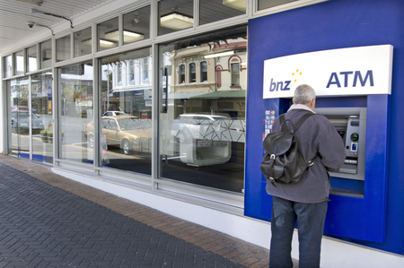 continuously: AUCKLAND - OCT 10:Man use Bank of New Zealand (BNZ) ATM Machine on Oct 10 2013.Its one of NZs largest banks and has been operating continuously in the country since October 1861.