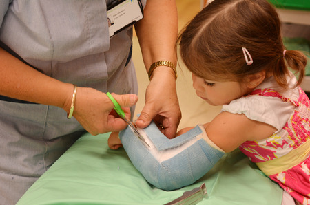 fractures: KAITAIA, NZ  - MAR 27 2014:Nurse removing an arm orthopedic cast of a child (Talya Ben-Ari age 3). Forearm fractures account for 40% to 50% of all childhood fractures.