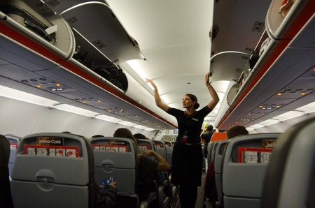 AUCKLAND - JAN 12:Flight attendant on Jan 12 2013. For planes with up to 19 passenger seats, no flight attendant is needed. For larger planes, one flight attendant per 50 passenger seats is needed. Redakční
