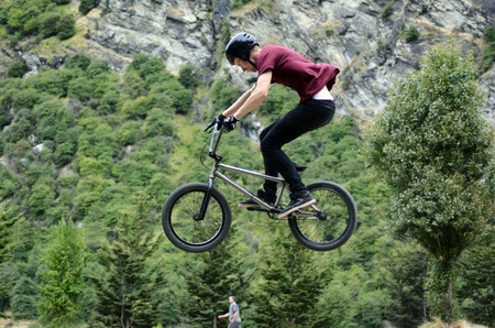 bmx bike: QUEENSTOWN, NZ - JAN 15:Young man performing tricks and stunts with his BMX Bike on Jan 15 2014.BMX riding became official Olympic sport in the 2008 Summer Olympic Games in Beijing, China. Editorial
