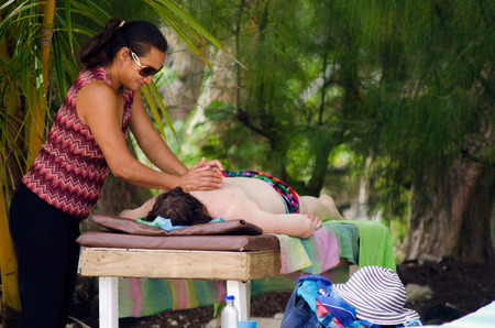 massagist: RAROTONGA - SEP 17:Cook Islander massagist massaging a tourist on the beach on Sep 17 2013.Massage is one of the oldest form of healthcare.