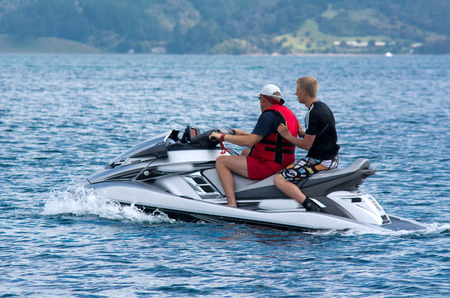 BAY OF ISLANDS,NZ - DEC 12:Two men rides personal water craft on Dec 12 2013.Operating a PWC can involve a risk of body orifice injuries and fuel discharge can contaminates the wildlife environment.