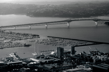 presently: AUCKLAND, NZ - OCT 08:Aerial view of Auckland harbor bridge on Oct 08 2013.The daily average number of cars crossing the Auckland Harbour Bridge is presently around 165,000.(BW)