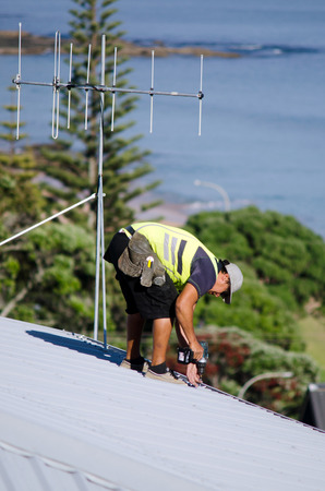 scaffolds: CABLE BAY,NZ:Roofer fixing a roof on Dec 12 2013. In 2000, 717 workers died of injuries caused by falls from ladders, scaffolds, buildings, or other elevations. Editorial
