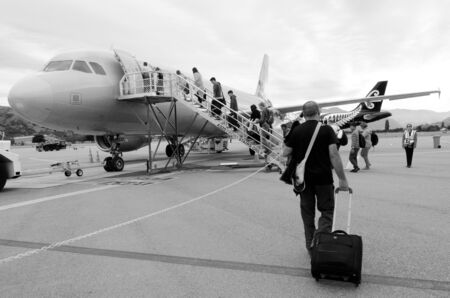 scheduled: QUEENSTOWN, NZ - JAN 18:Passengers board on a plane in Queenstown Airport on Jan 18 2014.Its the fourth busiest airport in NZ by passenger traffic handled 924,248 airline scheduled passengers in 2011. (BW) Editorial