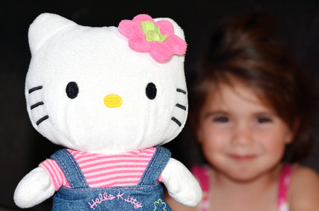 age 5: AUCKLAND, NZ - MAR 21 2014:Child (Talya Ben-Ari age 3) play with Hello Kitty figurine.At age 40 as of 2014, the product of the Japanese company Sanrio is a global phenomenon worth $5 billion a year Editorial