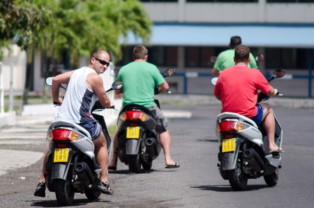 rarotonga: RAROTONGA - SEP 16:Young men rides motorbikes on Sep 16 2013.Its one of the must popular activity in the Island but Cook Islands Drivers License is required to operate a motorized rental.
