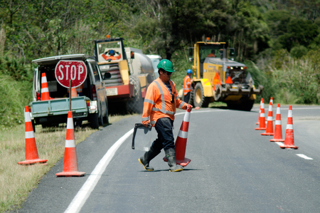 CABLE BAY, NZ - DEC 12:Road worker slows traffic with stop sign on Dec 12 2013.The Road Maintenance crew has the responsibility for the day-to-day maintenance needs of the road system. 報道画像