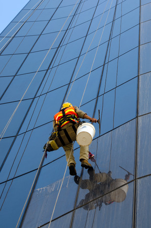 MELBOURNE - APR 14, 2014:Window cleaner works on high rise building.Window cleaning is considered one of the most dangerous job in the world.Several window cleaners die each year and many are injured Editorial