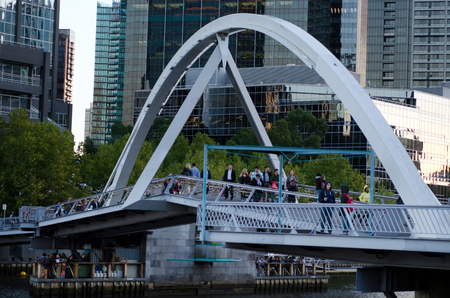southbank: MELBOURNE,AUS - APR 14 2014:People pass on the Southbank Foot Bridge.Its a very popular bridge that crossing the Yarra River and connect the South Bank to Melbourne  CBD for pedestrians and cyclists. Editorial