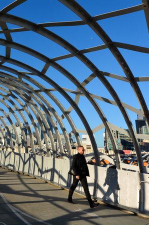webb: MELBOURNE,AUS - APR 14 2014:Pedestrian cross on Webb Bridge.Its an award winning bridge forming a cycling and pedestrian link to the main part of Docklands, through Docklands Park. Editorial