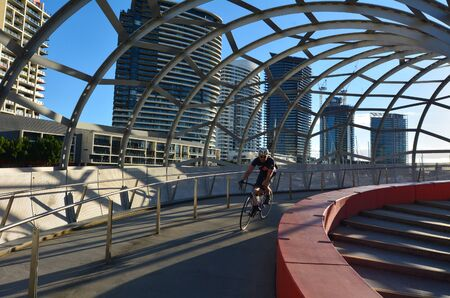 webb: MELBOURNE,AUS - APR 14 2014:Cyclist cross on Webb Bridge.Its an award winning bridge forming a cycling and pedestrian link to the main part of Docklands, through Docklands Park. Editorial