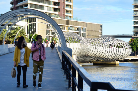 webb: MELBOURNE,AUS - APR 14 2014:Visitors cross on Webb Bridge.Its an award winning bridge forming a cycling and pedestrian link to the main part of Docklands, through Docklands Park. Editorial