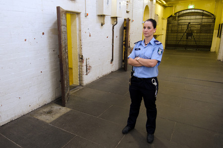 gaol: MELBOURNE - APR 11 2014:A woman jailer at the Old Melbourne Gaol, As of 2010, the gaol is recognized as Victorias oldest surviving penal establishment, and attracts approximately 140,000 visitors per year Editorial