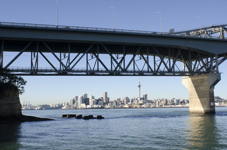 nz: AUCKLAND,NZ - MAY 27 2014:Auckland skyline trough Auckland Harbor Bridge.The daily average number of cars crossing the Auckland Harbour Bridge is presently around 165,000
