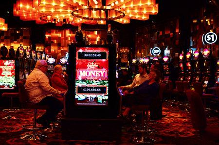 tragamonedas: MELBOURNE, AUS - 11 de abril 2014: Los visitantes jugar en las máquinas Gamble en el Crown Casino, el mayor complejo de casino de Melbourne.It en el Hemisferio Sur y uno de los más grandes del mundo.