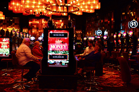 MELBOURNE, AUS - APR 11 2014:Visitors play on Gamble machines at Crown Casino, Melbourne.Its the largest casino complex in the Southern Hemisphere and one of the largest in the world. Editorial