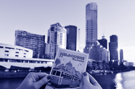 southbank: MELBOURNE - APR 14, 2014: Womans hand hold a postcard against Melbourne Southbank skyline.It is one of the primary business centers and also one of the most densely populated areas of Greater Melbourne. Editorial