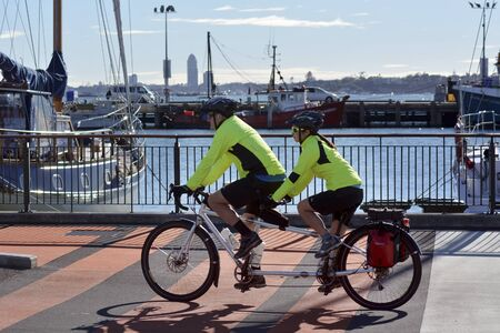 AUCKLAND,NZ - JUNE 01 2014:Couple rids tandem bicycle.Compared to a conventional bicycle, a tandem has double the pedalling power and with only slightly more frictional loss in the drivetrain. Editorial