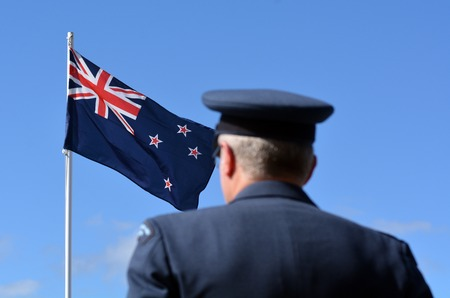 national military cemetery: MANGONUI, NEW ZEALAND - APRIL 25 2014: New Zealand Army officer stands under New Zealand flag during the National War Memorial service.
