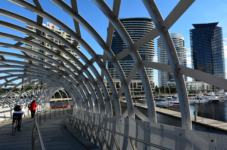 urban scene: MELBOURNE,AUS - APR 14 2014:Cyclist and pedestrian cross on Webb Bridge.Its an award winning bridge forming a cycling and pedestrian link to the main part of Docklands, through Docklands Park. Editorial