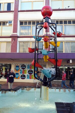 kinetic: WELLINGTON - AUG 22 2014:People pass by the Bucket Fountain, an iconic kinetic sculpture in Wellington, the capital city of New Zealand.